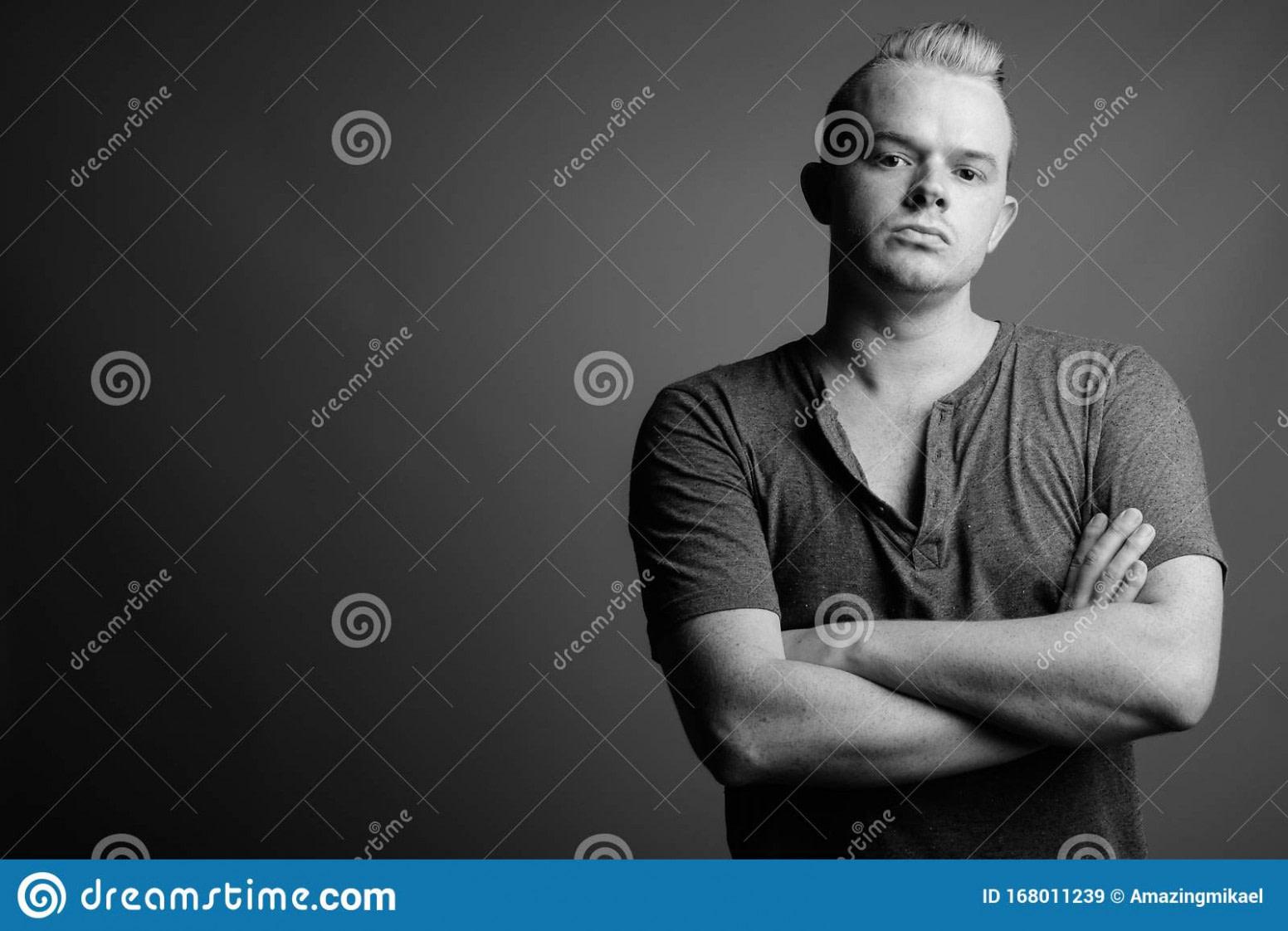 neu Mann Mit Mohawk-Frisur Und Blondem Haar Vor Graugrauem Hintergrund  - moderne irokesen frisur männer